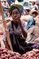 In a Rangoon, Myanmar, food market, a woman smoking a cigar waits for customers. food, street scene, trade, occupations, vendor, Burma. woman food merchant. Rangoon, Myanmar street food market.