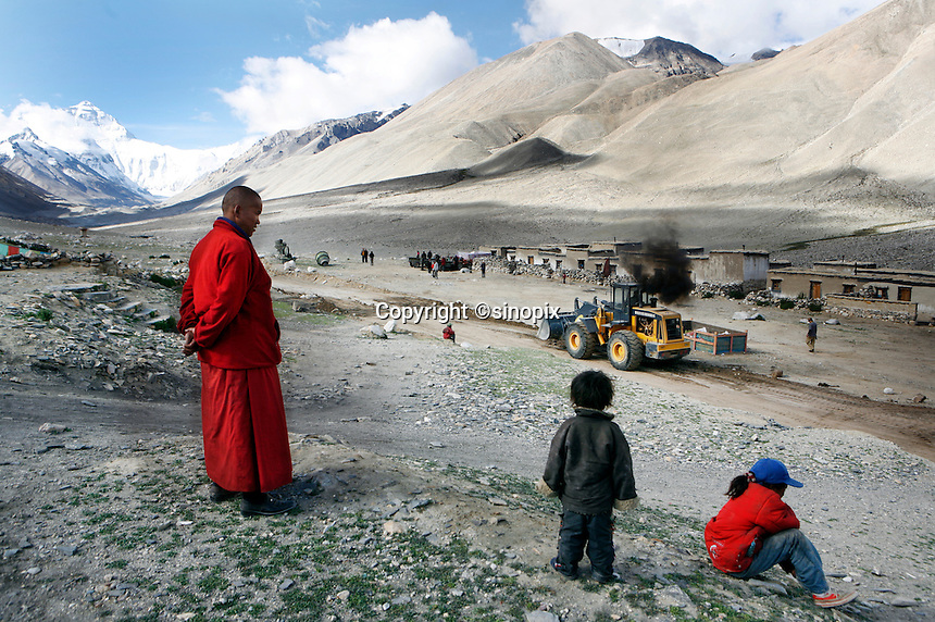 """A monk overlooks the roadworks in front of Rongbuk Monastery at Everest base camp.<br /> China started building a controversial 67-mile """"paved highway fenced with undulating guardrails"""" to Mount Qomolangma, known in the west as Mount Everest, to help facilitate next year's Olympic Games torch relay."""