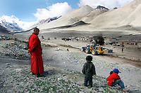 "A monk overlooks the roadworks in front of Rongbuk Monastery at Everest base camp.<br /> China started building a controversial 67-mile ""paved highway fenced with undulating guardrails"" to Mount Qomolangma, known in the west as Mount Everest, to help facilitate next year's Olympic Games torch relay."