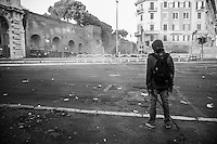 A hooded rioter faces a police deployment  holding  a iron bar as seen during the intense clashes nearby piazza San Giovanni.  Rome, Italy. 15/10/2011