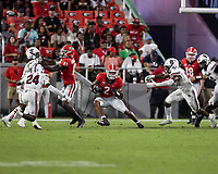ATHENS, GA - SEPTEMBER 18: Kendall Milton # 2 changes direction during a running play against defenders Marcellas Dial #24 and Brad Johnson #19 before a game between South Carolina Gamecocks and Georgia Bulldogs at Sanford Stadium on September 18, 2021 in Athens, Georgia.