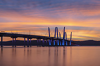 The Governor Mario M. Cuomo Bridge, illuminated in red, white, and blue in recognition of Columbus Day, spans the Hudson River just before sunset.