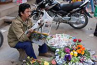 Kathmandu, Nepal.  Nepali Vendor of Flowers and Flower Seeds Reading Newspaper, Downtown Sidewalk Market.