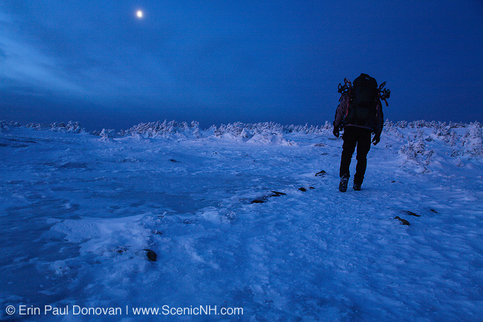 Hiker on the summit of Mount Pierce in the White Mountains, New Hampshire USA at dawn. Half moon can be seen in the background.