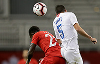 TORONTO, ON - OCTOBER 15: Alphonso Davies #12 of Canada and Daniel Lovitz #5 of USA battle in the air during a game between Canada and USMNT at BMO Field on October 15, 2019 in Toronto, Canada.