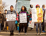 February 11, 2017. Raleigh, North Carolina.<br /> <br /> (left to right) Jasmine Michel, Jackie Michel and Tiffany Newkirk hold signs as they listen to the HKONJ speakers before the march.<br /> <br /> Thousands gathered in downtown Raleigh for the annual HKONJ People's Assembly, a civil rights march tied to the Moral Monday movement. Supporters from around the state gathered to march and speak out against nationwide attacks on civil rights and the Trump administration.<br /> <br /> Jeremy M. Lange for The New York Times