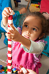 Education preschool 3-4 year olds making tower of cubes in a red and white pattern