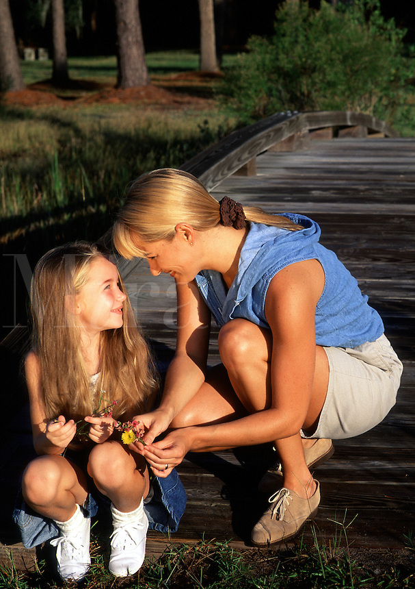 A mother and smiling young daughter on a dock.
