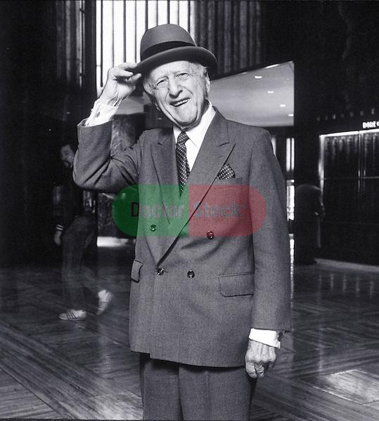 smiling elder man tipping his hat