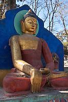 Kathmandu, Nepal.  Statue of the Buddha Guards the Stairs Leading to the Swayambhunath Temple Hilltop.