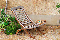 An old wooden garden lounge chair transat in a corner of the garden. Chateau Mourgues du Gres Grès, Costieres de Nimes, Bouches du Rhone, Provence, France, Europe