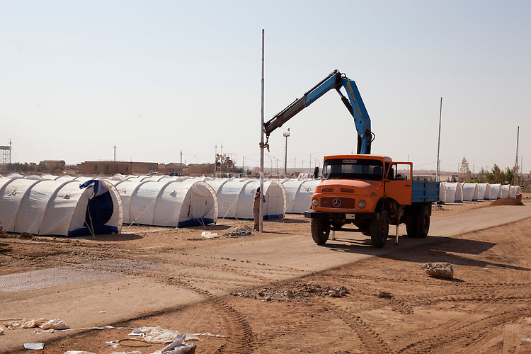 QAIM, IRAQ: Workers install a pole in the Qaim refugee camp for refugees fleeing the violence in Syria..Over 4,450 Syrian refugees have fled the violence in Syria and are living in the Qaim refugee camp in Iraq...Photo by Ali Arkady/Metrography
