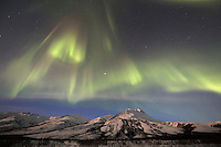 The aurora borealis swirls over the Brooks Range mountains, Arctic, Alaska.