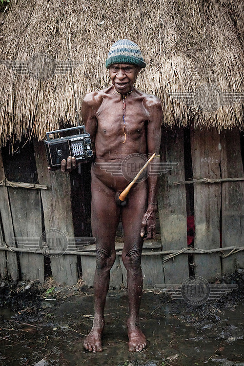 Iluga Lani, wearing a 'koteka' (a gourd penis sheath), is over 70 years old. He holds his radio receiver, which he bought for 280,000 Rupiah (GBP 14.81). It is the only modern thing he uses in his house.