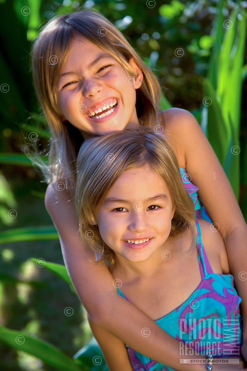 Two happy young sisters embrace in a garden on O'ahu.