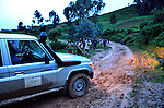 In rainy season, stuck in the mud at dusk in the mud on a mountain road in the western tea region of Rwanda. Villagers arrive to negotiate their services for giving us a needed push.