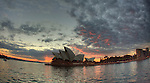 Arrival at Circular Quays by a Sydney Ferries coming from Manly  passing close by the Opera House, early in the morning with a cloudy sunrise.