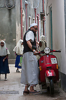 Stone Town, Zanzibar, Tanzania.  Arab Zanzibari and his Motor Scooter.  The colored hem of his kikoi (traditional under garment) can just be seen below his kanzu (white outer garment).