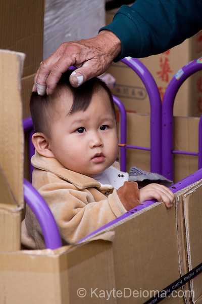 An aged hand with taped fingers rests on the head of a toddler standing in a playpen within a cardfboard box in Lugang, Taiwan