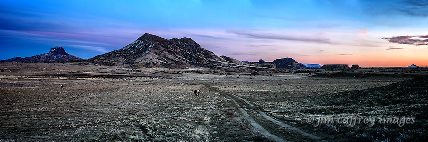 Cabezon Peak and Cerro Cuate dominate the skyline at twilight in New Mexico's Rio Puerco Valley.