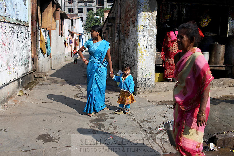 A woman and child wearing a matching shade of blue in a community in central Kolkata.<br /> <br /> To license this image, please contact the National Geographic Creative Collection:<br /> <br /> Image ID: 1925727 <br />  <br /> Email: natgeocreative@ngs.org<br /> <br /> Telephone: 202 857 7537 / Toll Free 800 434 2244<br /> <br /> National Geographic Creative<br /> 1145 17th St NW, Washington DC 20036