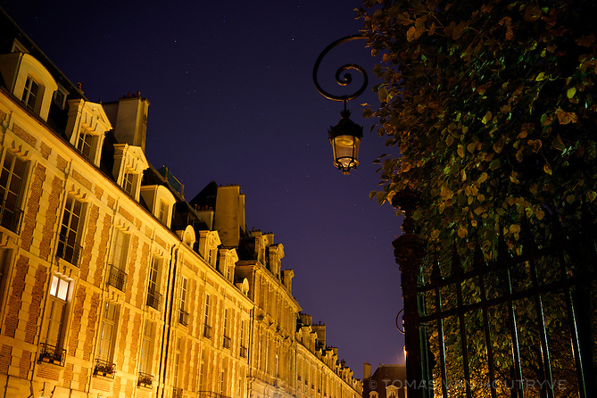 The Place des Vosges at night in the Marais neighborhood of Paris, France.