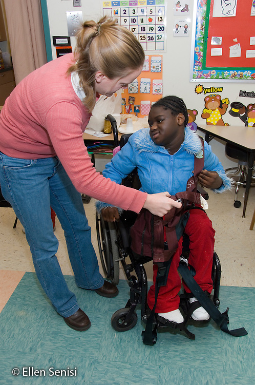 MR / Albany, NY.Langan School at Center for Disability Services .Ungraded private school which serves individuals with multiple disabilities.Teacher helps child in wheelchair remove chest harness used on the bus as she arrives at school. Girl: 10, African-American, cerebral palsy, expressive and receptive language delays.MR: Ris4; And6.© Ellen B. Senisi