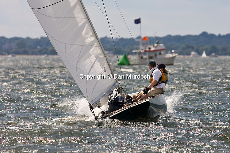 A racing Atlantic sailboat approaches the finish line