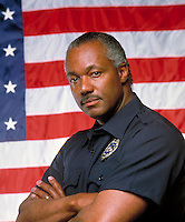 Uniformed, African American policeman standing in front of United States flag. Black man, occupations, law enforcement, uniform clothing, confident, pleasant, arms crossed, police. R. Williams M.R. # r-8.