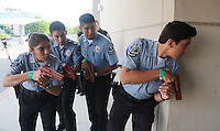 Lt. Sally Ortiz, Sgt. Jacob Chavez, Alejandro Barrios and Capt. Eric Molina prepare with guns drawn to enter a building with a reported active shooter.