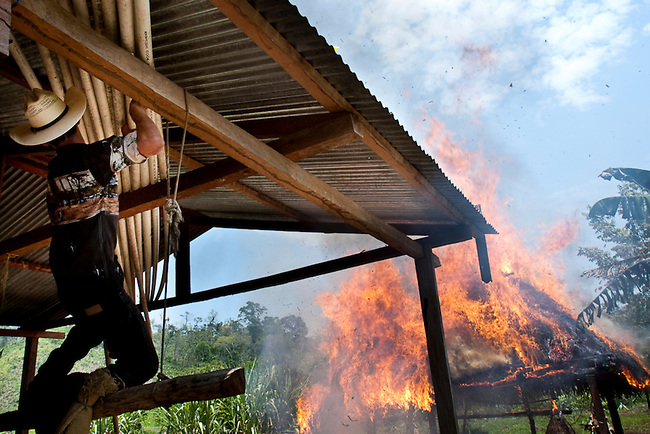 A rancher attempts to save plastic pipes after his house was set on fire when the Guatemalan police and the military evicted his family inside the Mayan Biosphere. Most evictions target poor people working for rich land owners who return within months of the evictions.