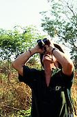 Luangwa National Park, Zambia. Tourist on safari watching birds with powerful binoculars.