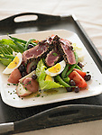 Niçoise salad with potato, tomato, lettuce, hard boiled eggs, green beans, and topped with slices of grilled ahi (yellowfin) tuna, cooked rare.