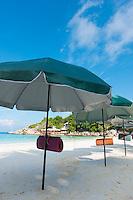 Open beach umbrellas in idyllic getaway, Raya island, Thailand