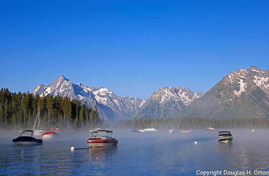 This image licensed exclusively by Spaces Images.  ID: DO_110729_Jackson_Lake_6425.jpg.  www.spacesimages.com.  Thank you.  Steam rises from Jackson Lake with the Grand Tetons as background in early morining, at Leeks Marina, Grand Teton National Park, United States, Wyoming.