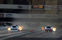 Nov. 10, 2012; Pomona, CA, USA: NHRA funny car driver Cruz Pedregon (right) races alongside Courtney Force during qualifying for the Auto Club Finals at at Auto Club Raceway at Pomona. Mandatory Credit: Mark J. Rebilas-