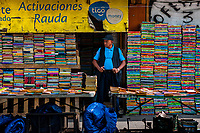 A Salvadoran bookseller stands in front of piles of used books stacked on the street in a secondhand bookshop in San Salvador, El Salvador, 9 April 2018. Large collections of worn-out books, mostly textbooks and educational paperbacks, are sold regularly in secondhand bookshops in the center of the city.