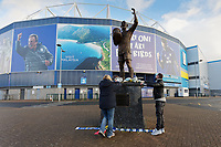 Pictured: A man and a woman pay their respects  the statue of Frederick Charles Keenor outside the Cardiff City Stadium in south Wales, UK. Tuesday 22 January 2019<br /> Re: Premier League footballer Emiliano Sala was on a flight which disappeared between France and Cardiff.<br /> The Argentine striker was one of two people on board the Piper Malibu, which disappeared off Alderney on Monday night.<br /> Cardiff City FC, signed the 28-year-old from French club Nantes.<br /> A search is under way.<br /> A Cardiff Airport spokeswoman confirmed the aircraft was due to arrive from Nantes but said there were no further details.<br /> HM Coastguard has sent two helicopters to help.