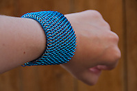 """A blue and silver dragonscale weave maille bracelet seen at an angle on an arm.  It's made from saw cut 18 gauge 1/4"""" ID blue anodized aluminum rings and saw cut 19 gauge 5/32"""" ID bright aluminum rings.  The clasp is a gunmental plated slide clasp.   Handmade by Michelle."""