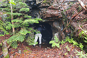 A hiker enters an old mine tunnel on Iron Mountain during the summer months in Jackson, New Hampshire USA. This tunnel is about 50 feet long.