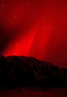 Intense red northern lights flare over the Tongass National Forest.