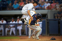 West Michigan Whitecaps relief pitcher Ryan Milton (26) collides with Jordan Serena (3) scoring a run on a passed ball during a game against the Burlington Bees on July 25, 2016 at Fifth Third Ballpark in Grand Rapids, Michigan.  West Michigan defeated Burlington 4-3.  (Mike Janes/Four Seam Images)