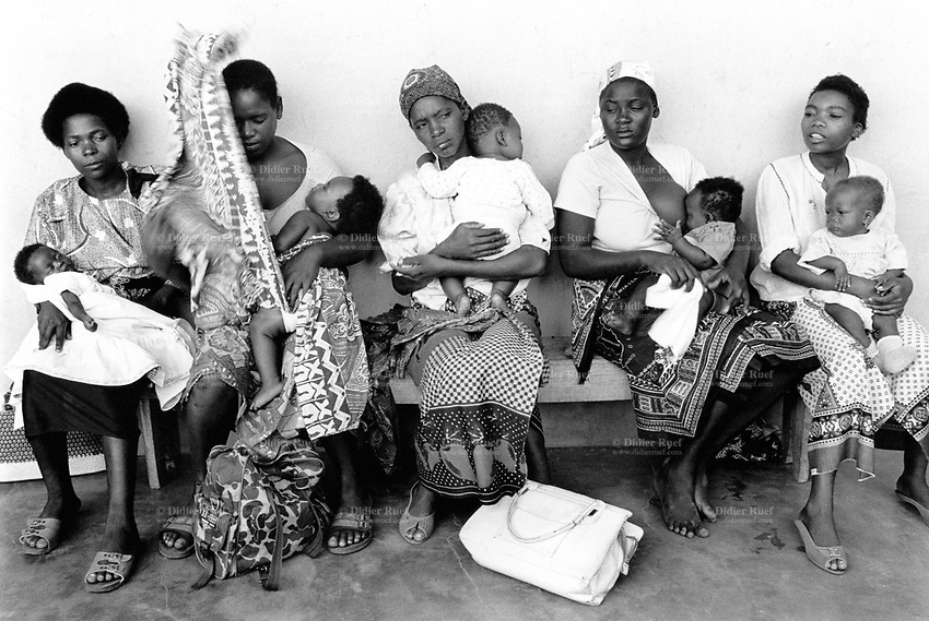 Mozambique. Province of Maputo. Maragra is a small village (80 km north of the capital Maputo). The non governmental organisation (ngo) Médecins Sans Frontières (MSF) of Switzerland has rehabilitated the local clinic. Mother and children are seated on a wood bench in the waiting room. They will be called for a medical consultation. © 1992 Didier Ruef