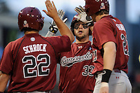 First baseman Kyle Martin (33) of the South Carolina Gamecocks, center, is congratulated by teammates Max Schrock (22), left, and Grayson Greiner (21) after hitting a three-run home run in the third inning of a game against the Furman Paladins on Tuesday, April 8, 2014, at Fluor Field at the West End in Greenville, South Carolina. South Carolina won, 9-2. (Tom Priddy/Four Seam Images)
