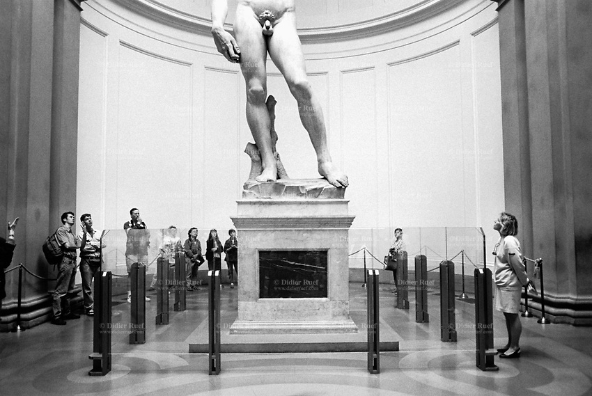 """Italy. Tuscany region. Florence. The Galleria dell'Accademia di Firenze, or """"Gallery of the Academy of Florence"""", is an art museum. David is a masterpiece of Renaissance sculpture created between 1501 and 1504, by the Italian artist Michelangelo. It is a 5.17-metre marble statue of a standing male nude. The statue represents the Biblical hero David, a favoured subject in the art of Florence. Originally commissioned as one of a series of statues of prophets to be positioned along the roofline of the east end of Florence Cathedral, the statue was placed instead in a public square, outside the Palazzo della Signoria, the seat of civic government in Florence, where it was unveiled on 8 September 1504. Because of the nature of the hero that it represented, it soon came to symbolize the defense of civil liberties embodied in the Florentine Republic, an independent city-state threatened on all sides by more powerful rival states and by the hegemony of the Medici family. The statue was moved to the Accademia Gallery in Florence in 1873, and later replaced at the original location by a replica. 10.04.93 © 1993 Didier Ruef"""