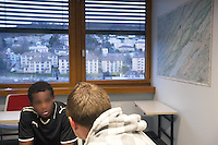 """Switzerland. The Republic and Canton of Neuchâtel. Neuchâtel. Police station headquarters. Narcotics squad. """"Narko"""" operation. A police officer in plainclothes is interrogating a black man from Western Africa who was arrested while selling cocaine in the streets. Plainclothes law enforcement is a method used by police. The policemen wear plainclothes or """"ordinary clothes"""" instead of a uniform in order to avoid detection or identification as law enforcement agents. A police station or station house is a building which serves for police officers. The building contains temporary holding cells and interview/interrogation rooms. 1.04.15 © 2015 Didier Ruef"""