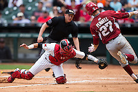 Tucker Pennell (27) of the Arkansas Razorbacks avoids the tag attempt of Texas Tech Red Raiders catcher Kholeton Sanchez (15) during game seven of the Shriners Hospitals for Children College Classic at Minute Maid Park on February 28, 2016 in Houston, Texas.  The Razorbacks defeated the Red Raiders 10-6.  (Brian Westerholt/Four Seam Images)