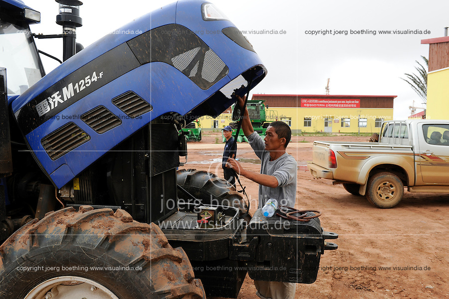 ANGOLA Malanje Black Stone Farm, eine 20.000 Hektar grosse Farm der chinesischen Firma CITIC construction corporation und der angolanischen Agentur Gesterra, die den Ausbau von Grossfarmen in Angola foerdert, Reparatur eines chinesisches Traktor / ANGOLA Malanje Black Stone Farm, a 20.000 hectare farm of chinese company CITIC construction corporation and angolian agency Gesterra which promotes large scale farms in Angola, repair of chinese tractor