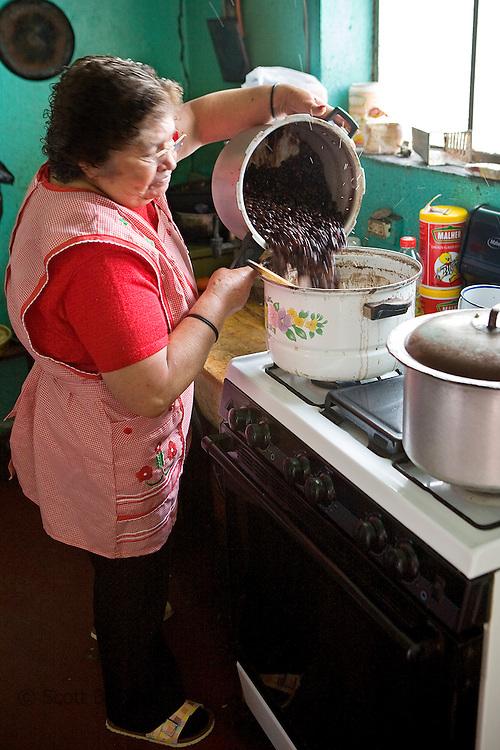 Guatemalan woman pours beans into a pot on the stove in her kitchen, Quetzaltenango, Guatemala