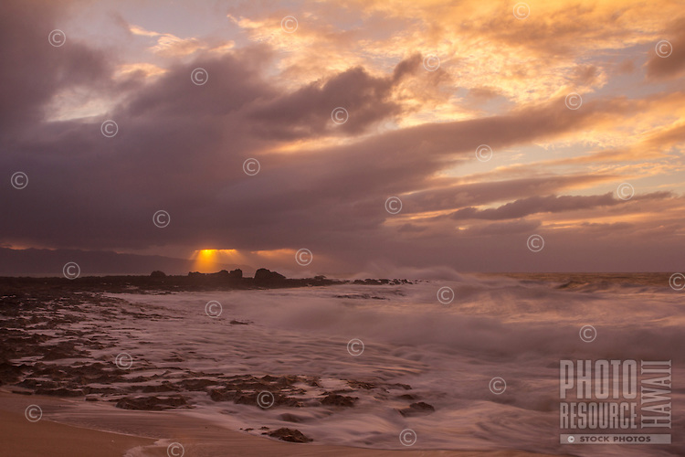 A stormy sunset scene with sun rays breaking through the clouds at Ke Iki, North Shore, O'ahu.
